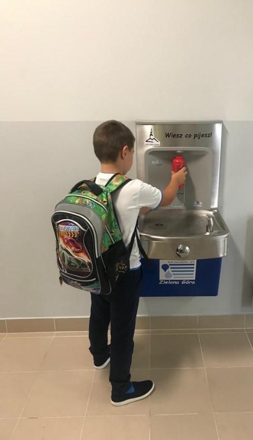 dziecko nalewa wody z poidelka
